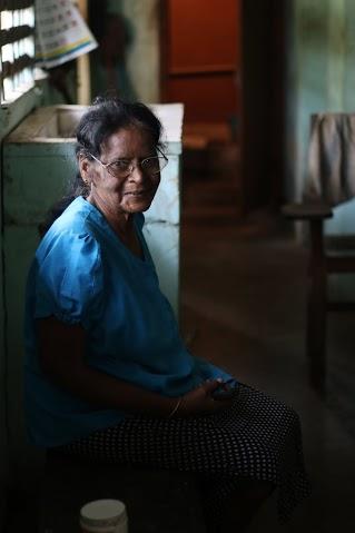 這位女士的生命故事令人肅然起敬, 她在1960年代完成科學學士學位, 於中學執教35年後戰爭爆發, 她流離失所近十年, 2008年戰事加劇後她守著自己在鎮上的補習班與自宅不願離開, 如今她仍在受損的屋室中開設英語與僧加羅與課程, 她至今未婚