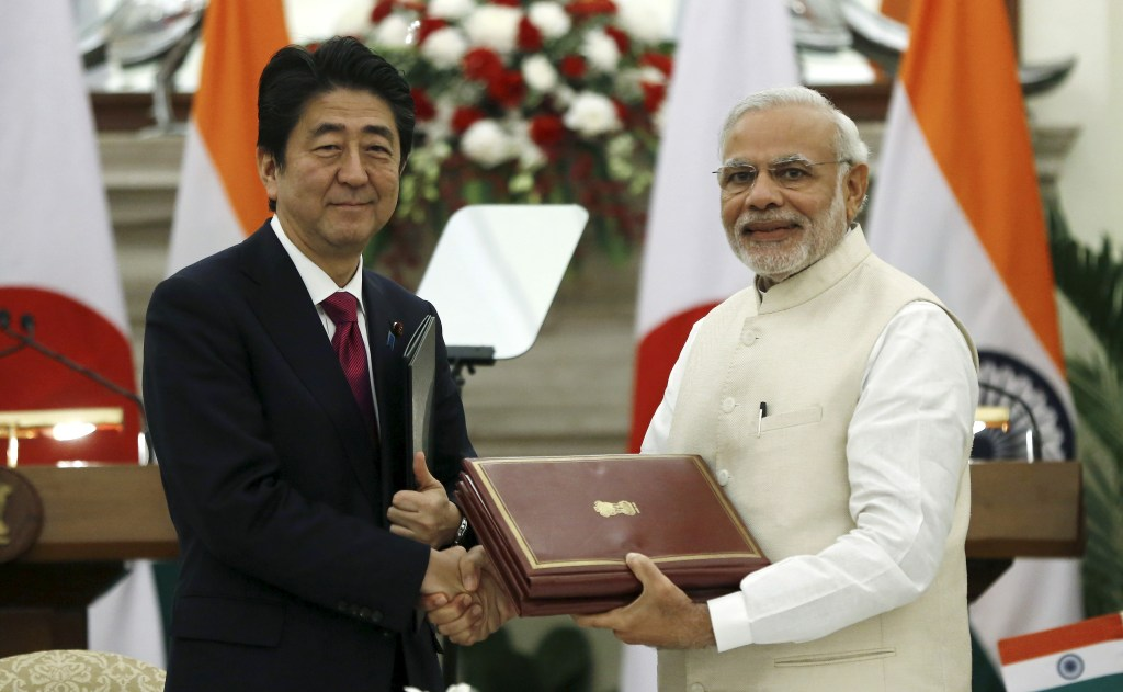 Japan's Prime Minister Shinzo Abe (L) and his Indian counterpart Narendra Modi shake hands while exchanging documents during a signing of agreement at Hyderabad House in New Delhi, India, December 12, 2015. India and Japan are likely to finalize an agreement on protection of military information during Abe's trip beginning on Friday that will the lay the ground for Japanese arms sales to India, including seaplanes. REUTERS/Adnan Abidi - RTX1YBZ6
