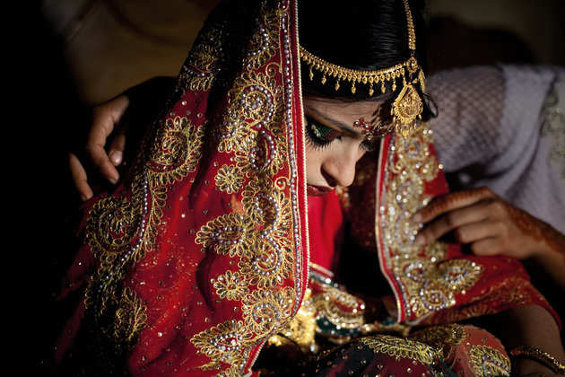 "MANIKGANJ, BANGLADESH - AUGUST 20: 15 year old Nasoin Akhter is consoled by a friend on the day of her wedding to a 32 year old man, August 20, 2015 in Manikganj, Bangladesh. In June of this year, Human Rights Watch released a damning report about child marriage in Bangladesh. The country has one of the highest rates of child marriage in the world, with 29% of girls marrying before the age of 15, and 65% of girls marrying before they turn 18. The detrimental effects of early marriage on a girl cannot be overstated. Most young brides drop out of school. Pregnant girls from 15-20 are twice as likely to die in childbirth than those 20 or older, while girls under 15 are at five times the risk. Research cites spousal age difference as a significant risk factor for violence and sexual abuse. Child marriage is attributed to both cultural tradition and poverty. Parents believe that it ""protects"" girls from sexual assault and harassment. Larger dowries are not required for young girls, and economically, women's earnings are insignificant as compared to men's. (Photo by Allison Joyce/Getty Images)"