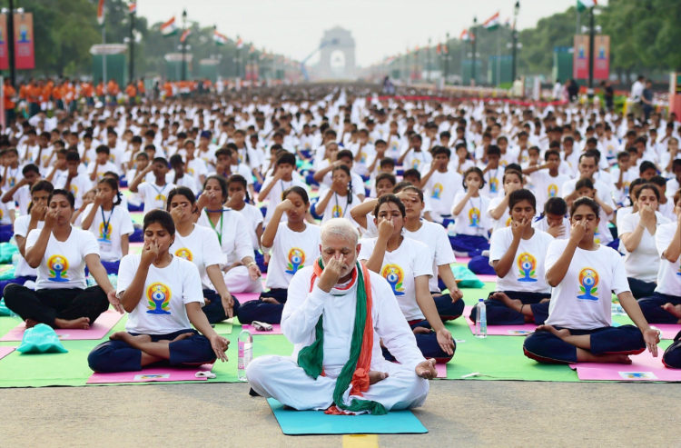 New Delhi: Prime Minister Narendra Modi wipes his sweat during a mass yoga session on the International Day of Yoga 2015 at Rajpath in New Delhi on Sunday. PTI Photo by Manvender Vashist (PTI6_21_2015_000185A)