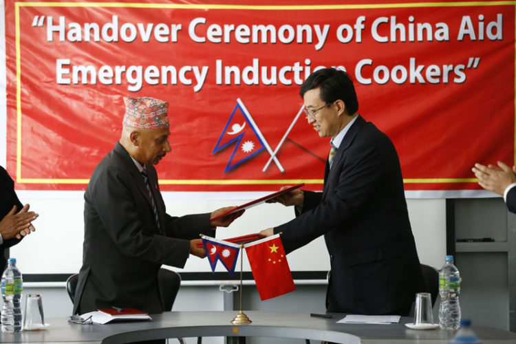 Chinese Ambassador Wu Chuntai (right) shaking hands with Secretary at the Ministry of Supplies Shreedhar Sapkota after handing over 10,000 induction heaters to Nepal government, in Kathmandu, on Wednesday. THT